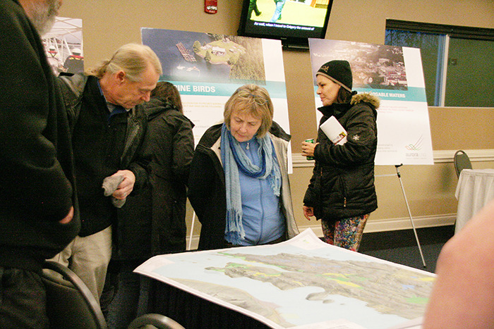 Members of the public and Dodge Cove residents examine the maps laid out by Aurora LNG staff at last week's open house in Prince Rupert. Aurora LNG was receiving public comment regarding their proposed site on Digby Island. - Kevin Campbell